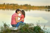Little girl hugging her mother near the lake — Stock Photo