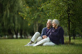 Mature couple sitting on green grass — Stock Photo