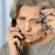 Pensive elderly woman calling on the phone — Stock Photo #53509845