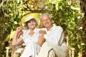 Senior couple in garden on bench — Stock Photo