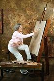 Zralý ženský umělec maluje — Stock fotografie