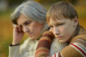 Sad grandmother with boy  in the park — Stock Photo