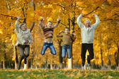 Elderly couple and children jumping — Stock Photo