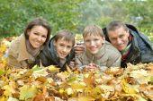 Happy family lying in autumn park — Stock Photo