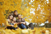 Family sitting  in autumn park — Stock Photo