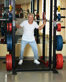 Elderly man playing sports in a gym — Foto Stock