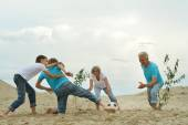 Family playing football on a beach — ストック写真