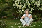 Older woman under bush — Zdjęcie stockowe