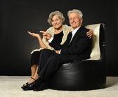 Senior couple sitting on black cushions — Stok fotoğraf