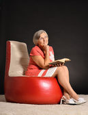 Happy senior woman reading book — Стоковое фото