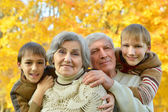 Grandparents and grandchildren in autumn park — Stock Photo