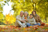 Happy family relaxing in autumn forest — Stock Photo