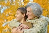 Grandmother with boy  in autumn park — Stock Photo