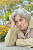 Sad old woman in park — Stock Photo