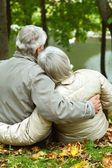 Mature couple sitting near lake — Foto de Stock