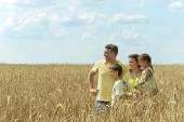 Family standing on wheat field — Stock Photo