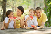 Family eating a watermelon — Stock Photo