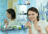 Woman  makes her make up — Stock Photo