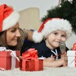 Mother with boy near Christmas tree — Stock Photo #59850723
