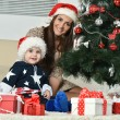 Mother with boy near Christmas tree — Stock Photo #59851293