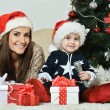 Mother with boy near Christmas tree — Stock Photo #59851659