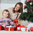 Mother with boy near Christmas tree — Stock Photo #59851733