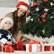 Mother with boy near Christmas tree — Stock Photo #59851925