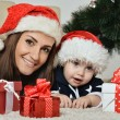 Mother with boy near Christmas tree — Stock Photo #59852169