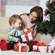 Mother with boy near Christmas tree — Stock Photo #59852867