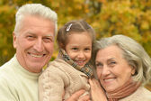 Grandparents with girl in forest — Stock Photo