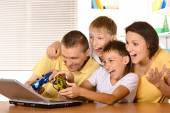 Family playing on laptop — Stock Photo
