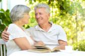 Older couple reading a book — Stockfoto