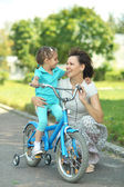 Girl on a bicycle with  mother — Stock Photo