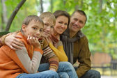 Family  on a bench in park — Stock Photo