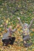 Elderly couple throwing leaves — Stock Photo