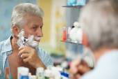 Senior man shaving in bath — Stock Photo