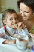 Mother and daughter eating soup — Stock Photo