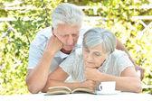 Older couple reading a book — ストック写真