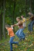 Family running in autumn park — Stock Photo