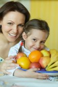 Mother and daughter eating fruits — Stock Photo