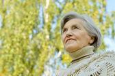 Elderly woman in autumn park — Stock Photo