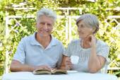Old couple with  drink and book — Stock Photo
