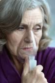 Senior woman with inhaler — Stock Photo