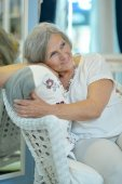 Elderly woman sitting in chair — Stock Photo