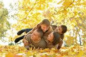 Family lying in autumn park — Stock Photo