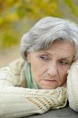 Sad old woman in autumn — Stockfoto