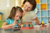 Little girl painting with  mother — Stockfoto