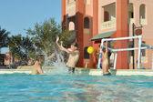 Pai e filhos jogando pólo aquático — Fotografia Stock