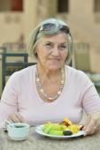 Beautiful elderly woman in cafe — Stock Photo