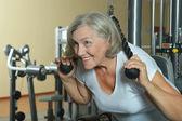 Elderly woman exercising in gym — Stock Photo